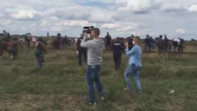 Hungarian journalist Petra Laszlo (blue shirt) trips a fleeing syrian refugee holding a child in an effort to get a good shot, causing him to be arrested by police. She was also taped kicking at other refugees