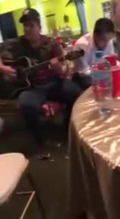 Some sicarios from from sinaloa cartel dressed in military fatigues., also drinking on the job enjoying some live music