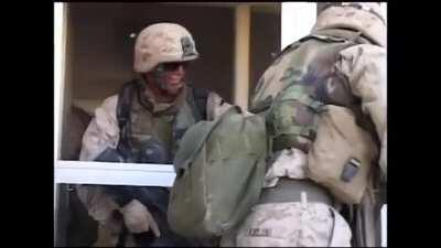 Marines find an insurgent hiding inside of a large building in Fallujah. They break the window and give him a grenade as a gift. Afterwards they make entry into the building and finish clearing it.