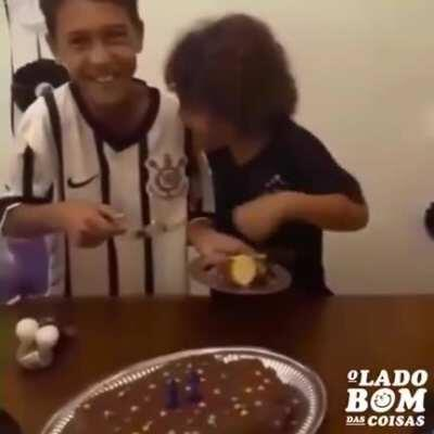 Little brother's reaction upon receiving the first piece of his brother's birthday cake.