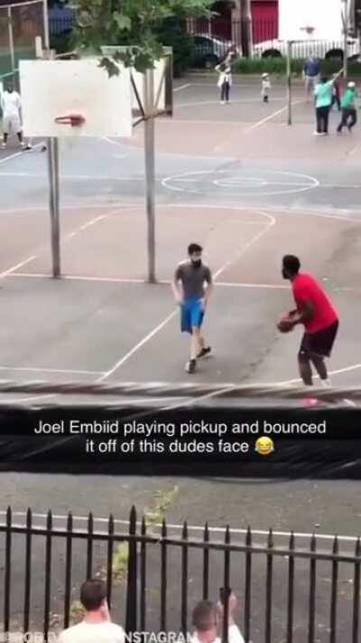 NBA Player Joel Embiid dunking on a random hooper