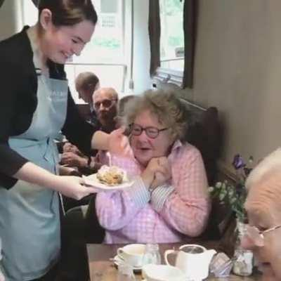 Sweet lady reacting to a free birthday cake at a diner she regularly visits.