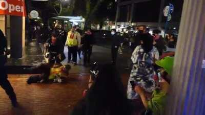 An officer aggressively shoved a protester to the ground when he was complying with their order.
