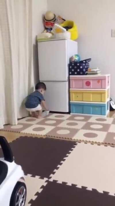 The refrigerator keeps giving the kid a hard time.