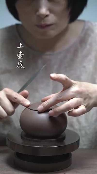 A lady making a teapot, she is so happy about it