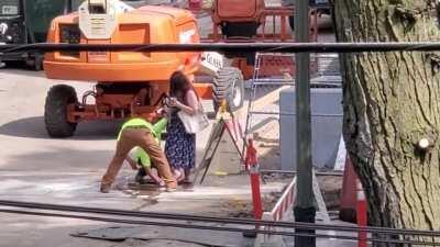 Construction workers washing off a blind woman's shoes after she walk through there site.