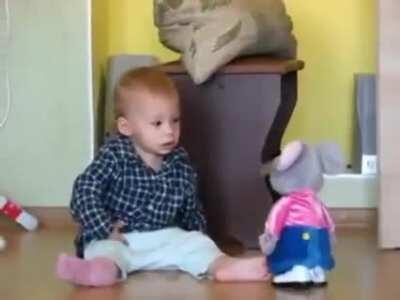Baby getting scared by a walking toy mouse