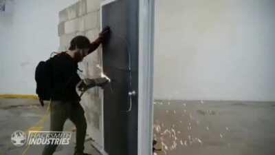 The Hacksmith uses a wrist mounted plasma torch to cut through a steel door.