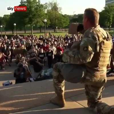 A National Guard officer hugged protesters after taking a knee with them.