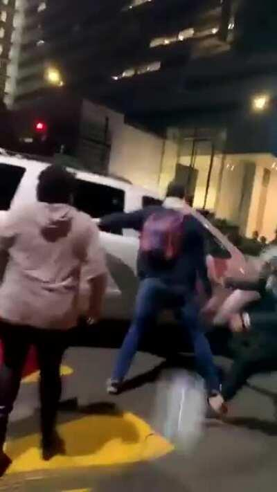 Guy stands behind a car as other people attack it from the front