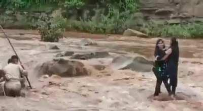 Two girls enter a flooding river to take selfies, get stuck.