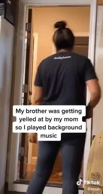 His brother was getting yelled by thier mother so he thought that playing some background music would be a good idea