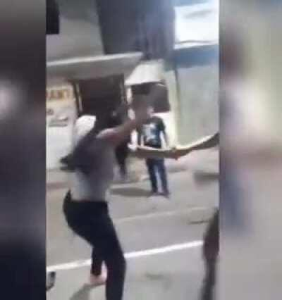 Stray dog pulls down woman's pants as she brawls with another in the street