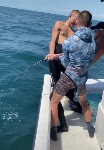 Three Bros Holding The Line To Reel In A Monster Grouper
