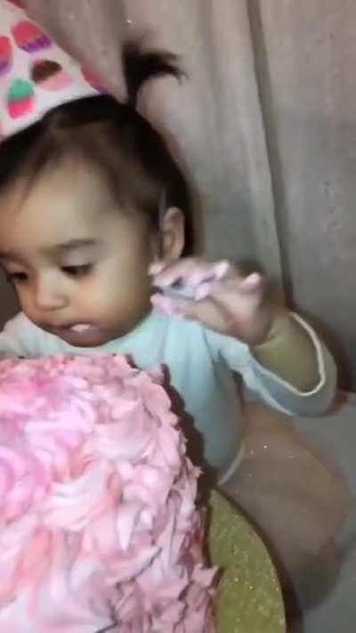Pushing baby's face into birthday cake