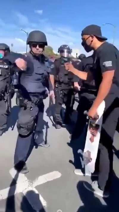Riot cop grabs and throws a protestor's phone. Protestor bitch slaps him into next Tuesday and legs it.