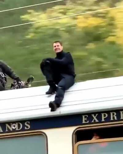 Tom Cruise chilling on top of a train whilst filming Mission Impossible 7