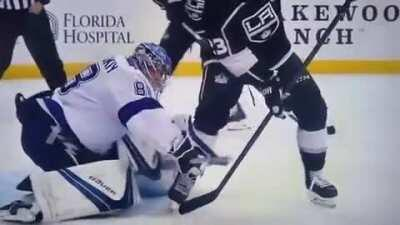 Lightning Goaltender Andrei Vasilevskiy looks between his opponent's legs to locate puck and make behind the back glove save