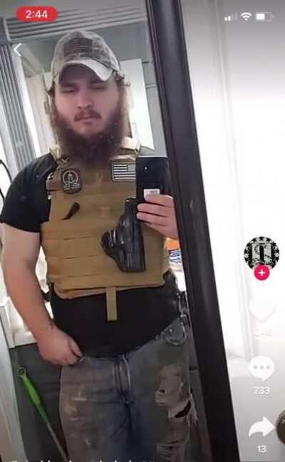 Fat guy with empty holster throws up the white power hand symbol