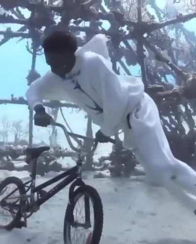 A guy takes his diving gear off to take a photo with his BMX bike at the bottom of the ocean