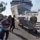 Several people are almost crushed by a ship that crashes against a docked boat