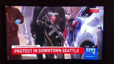 A man disarms a rioter that took a rifle out of a police cruiser in Seattle