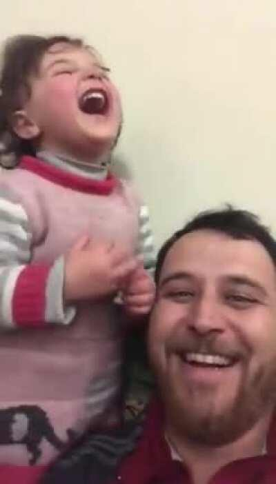 To distract his 4-year old daughter, her father has made up a game. Each time a bomb drops in Idlib Syria, they laugh, so she doesn't get scared.