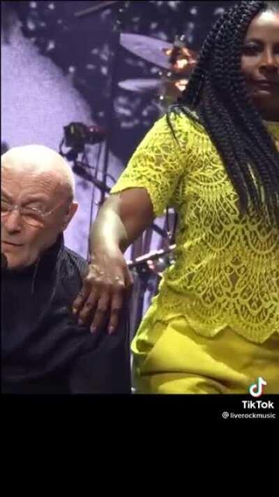 Phil Collins seems positively repulsed with a performer he's sharing the stage with