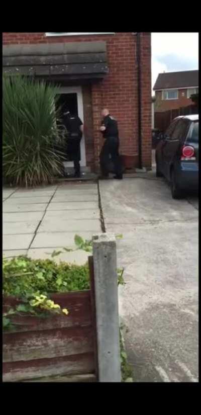 British Police knock down guys door, he escapes through the top floor window.