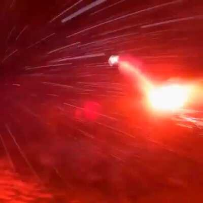 Man wingsuits off a mountain in a blizzard with a road flare at night.