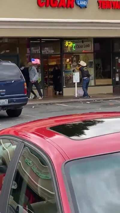 Cigar shop owner defends store, forcing looters out with his handgun.