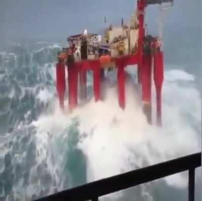 Massive waves hit an offshore oil rig