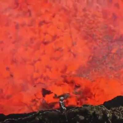 A man inside the crater of an active volcano.