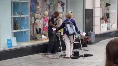 Woman in Liverpool tries to stop a busker earning a crust.