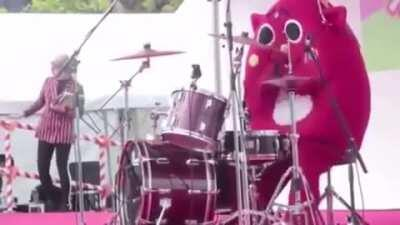 A costumed drummer completely destroying the drums