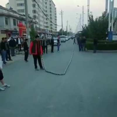 Guy whipping a giant chain