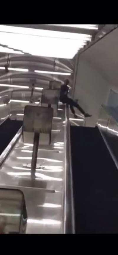 Sliding down an escalator handrail