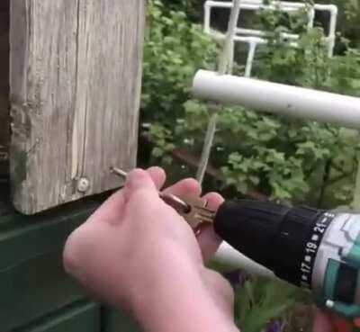 Using a power drill and a key to screw in the hook.