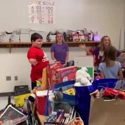 Students surprise a boy with toys after he lost all of his in a fire