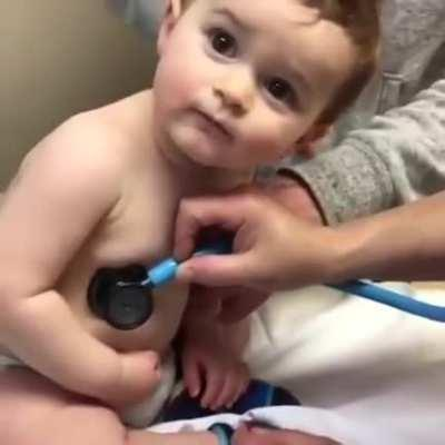 Cute baby resting it's head on doctor's hand.